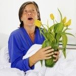 woman in her fifties sitting in bed and holding a vase with flowers