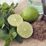 ingredients for a classic mojito cocktail sit on a breadboard