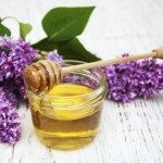 Lilac flowers with honey  on a wooden background