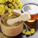 mortar, pestle,  healthy tea and bucket with coltsfoot flowers, herbal medicine