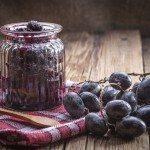 Dark grape jam on a wooden table.