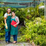 Portrait of plant nursery owners standing in front of greenhouse