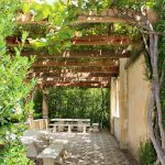 Vines covering the pergola, over a tiled picnic area.  Stone/marble bench and seats.  Taken on a gorgeous summers day in Hamilton Gardens, New Zealand